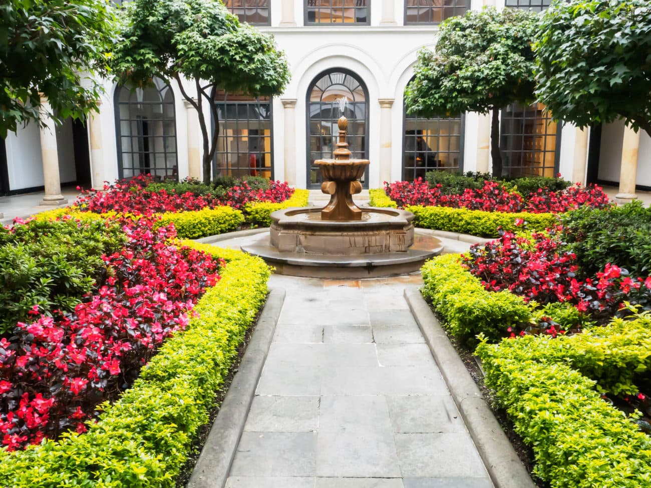 Courtyard of the Botero Museum, with white arches and a fountain