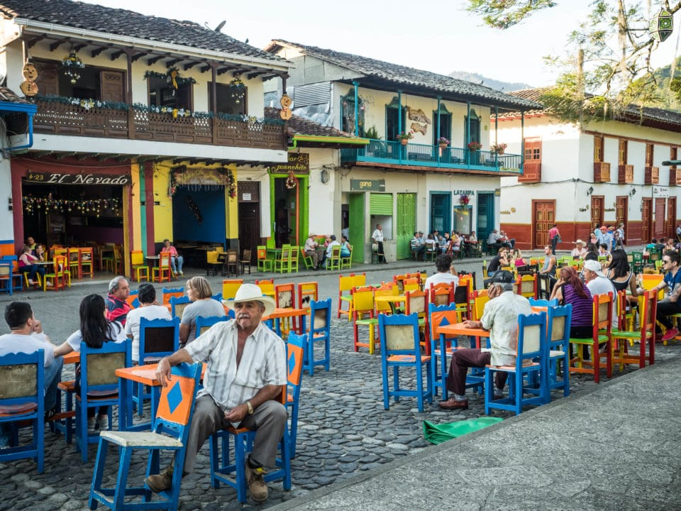 People sitting at colorful tables in Jardin plaza