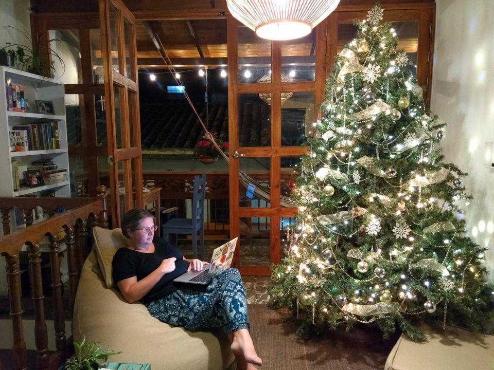 Melissa reading in a beanbag chair beside a bright Christmas tree