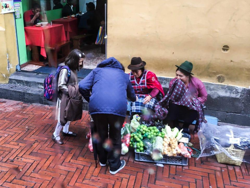 Andean woman seeing fruit on sidewalk