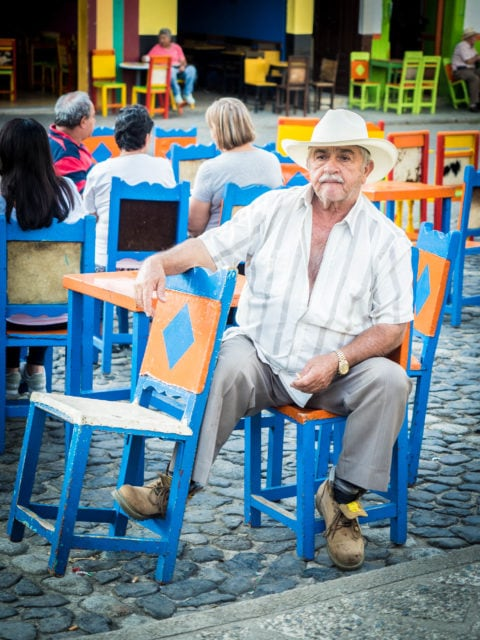 Man in cowboy hat sitting at a colorful table in the plaza