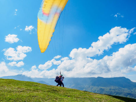 Melissa and her paraglider pilot taking off