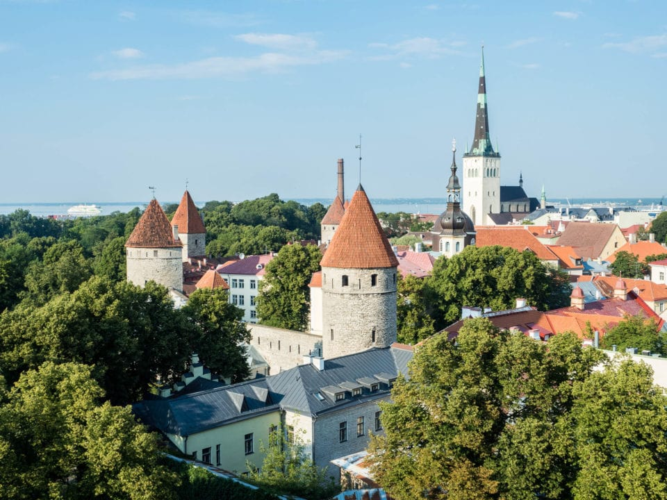 Tallinn skyline of red tiled roofs, trees, and church towers