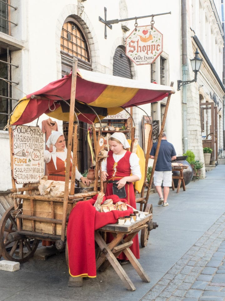 Two women in medieval costume selling candy from wooden cart
