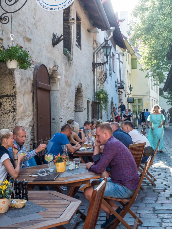 People eating at cafe tables on cobbled street