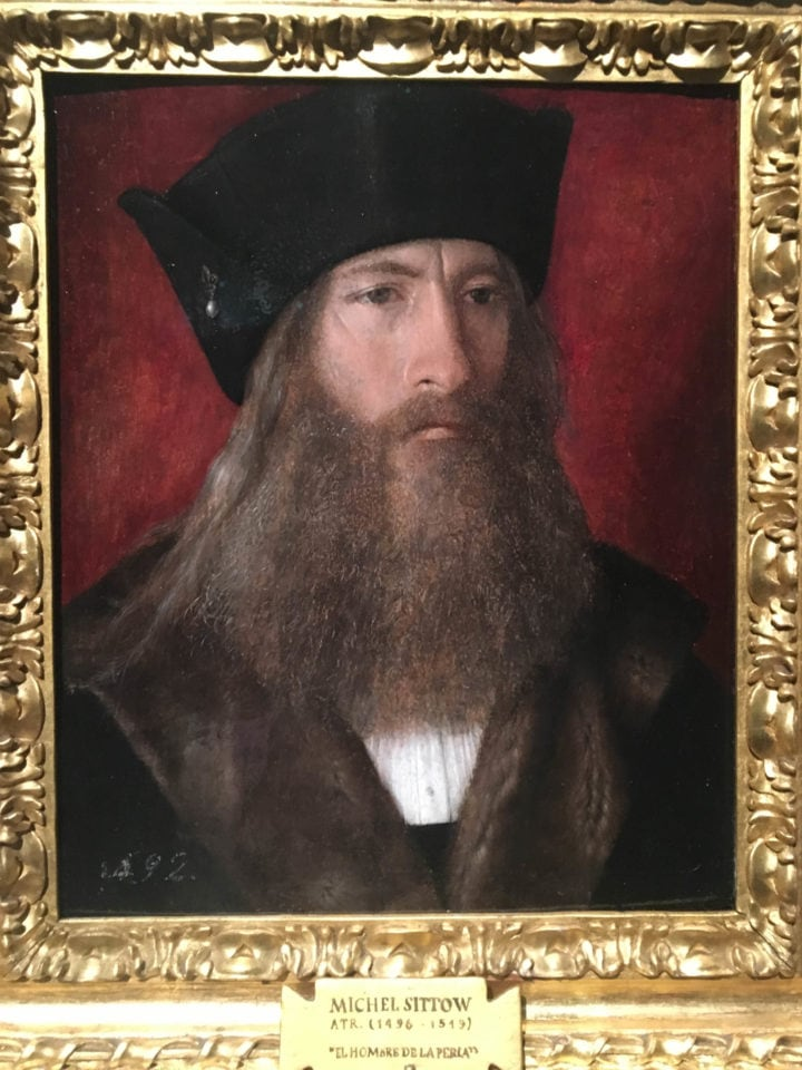 Oil painting in gold frame of man in black with large beard
