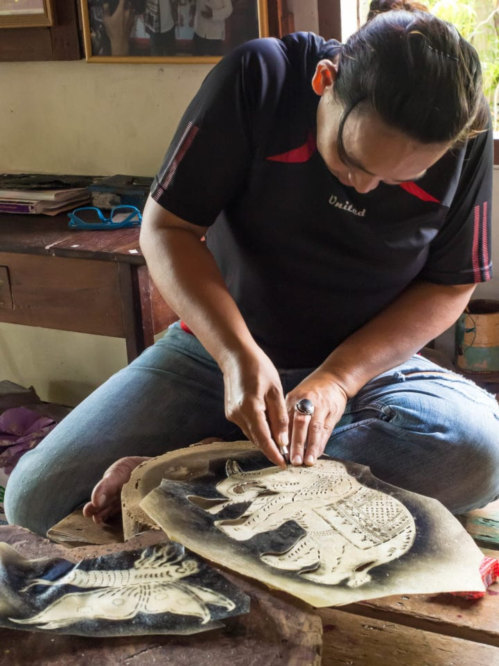 Woman making a leather shadow puppet