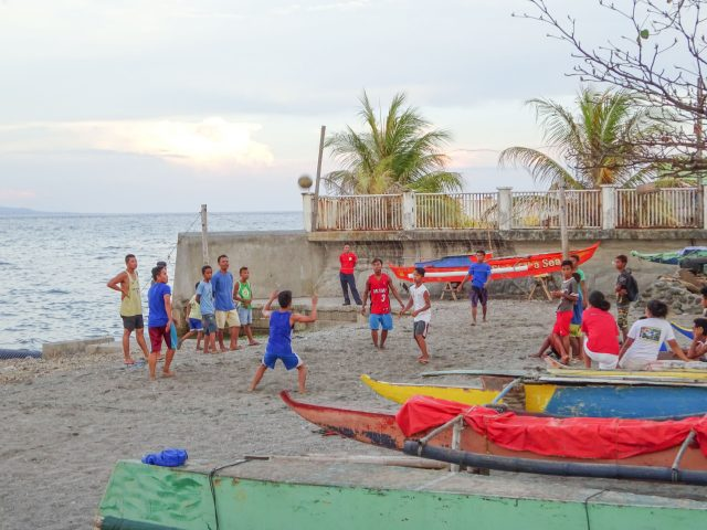 Guys playing volleyball on beach in Dumagete
