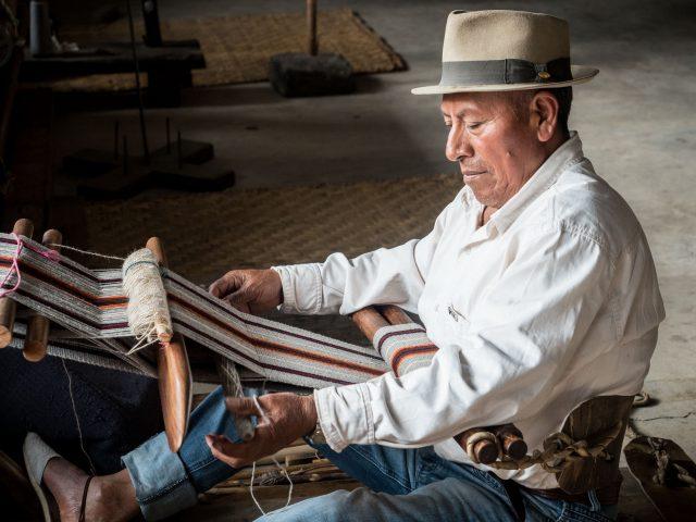 Man in hat weaving with backstrap loom