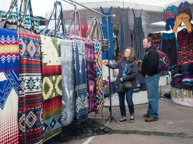 Tourists shopping for rugs at Otavalo market