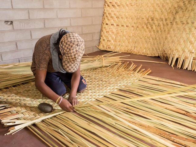 Boy weaving reed mats