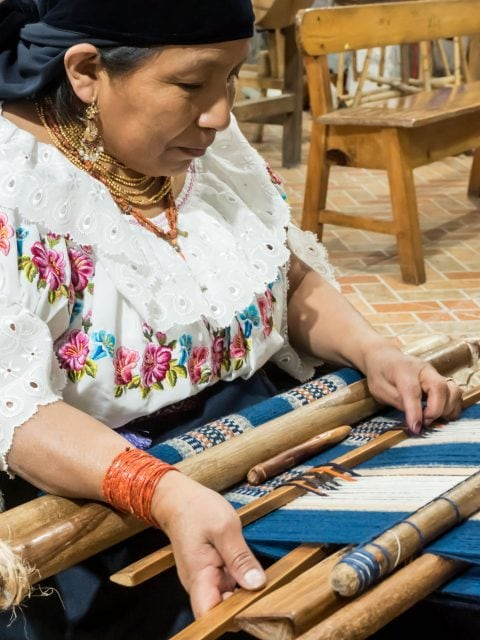 Otavalo woman in traditional dress  weaving a rug