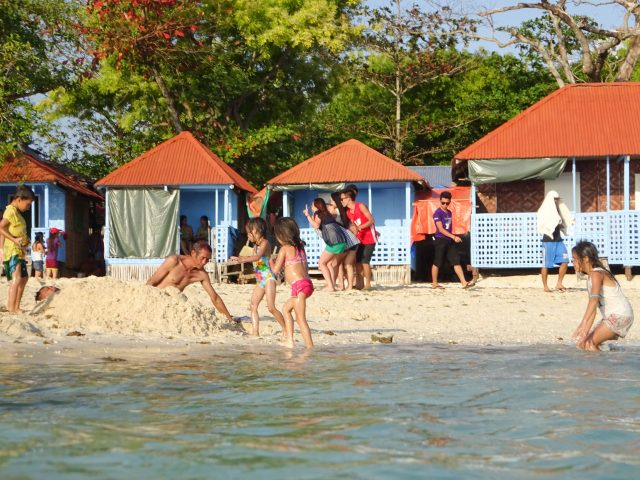 People playing on beach in front of little cottages