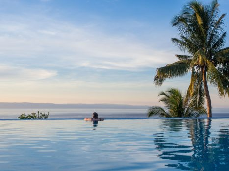 Infinity pool with palm trees and clouds in distance