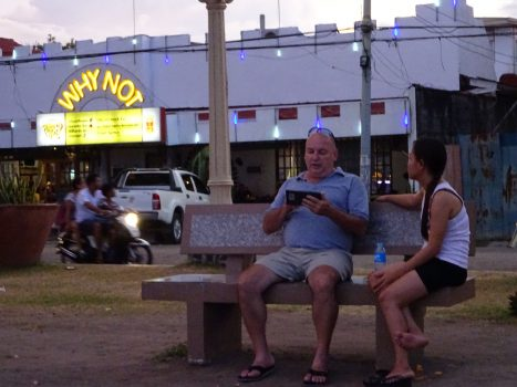 Middle-aged Western man sitting on bench with younger Filipino woman