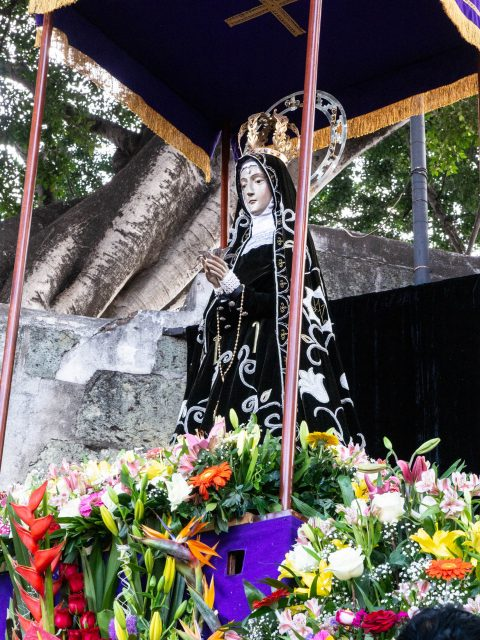 Madonna statue under canopy with flowers