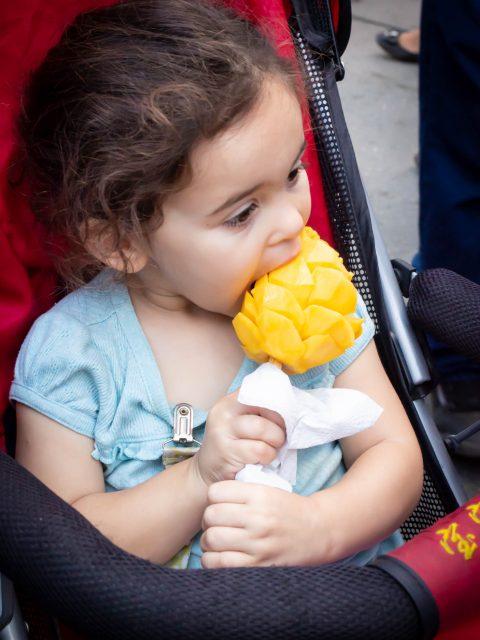 Francesca eating a peeled mango on a stick