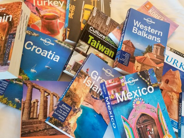 Piles of different travel guides