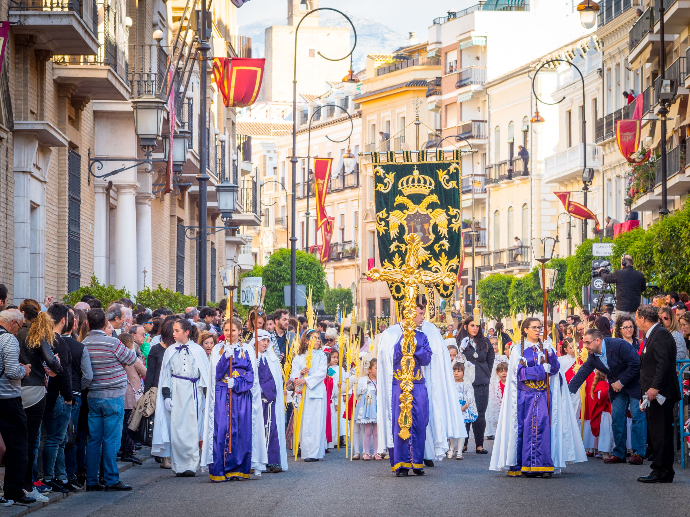Palm Sunday procession with gold cross and banners