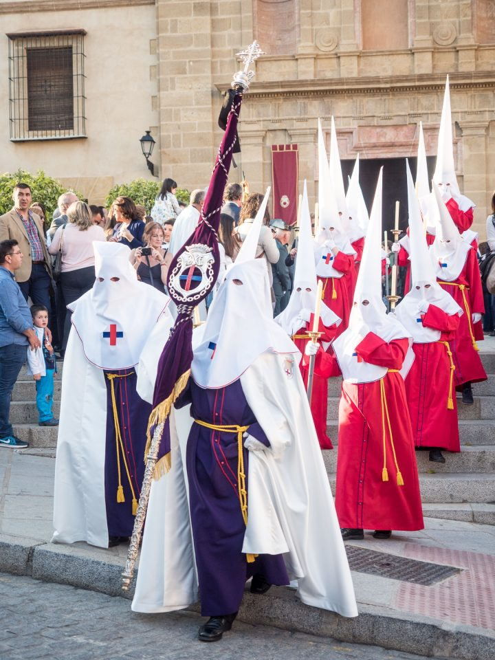 Nazarenos in red or purple robes and white pointed hoods with eye slits