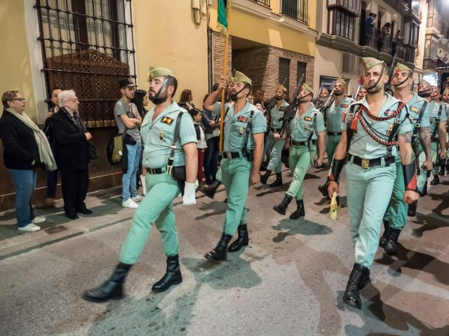 Members of Spanish Legion march in green uniforms with rifles