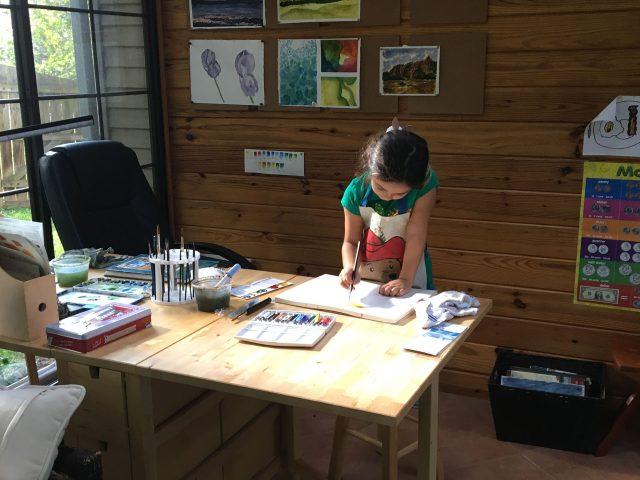 Francesca at a desk full of art supplies
