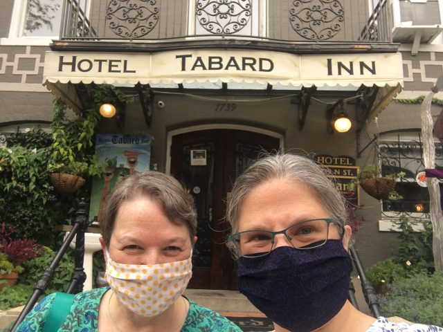Chris and Melissa wearing masks in front of the Hotel Tabard Inn