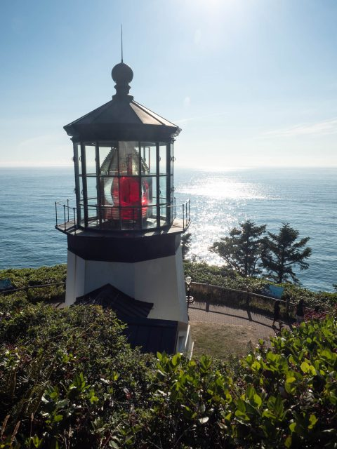 Top of lighthouse with red lantern bulb and sunlit ocean behind it