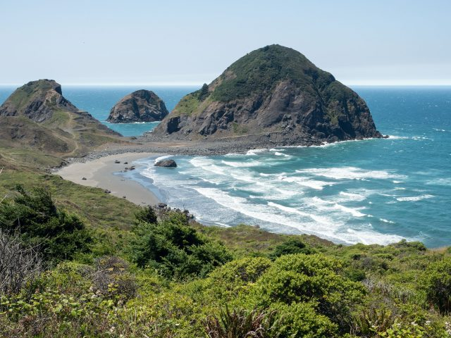 Curve of shoreline with greenery, waves, and triangular sea stacks