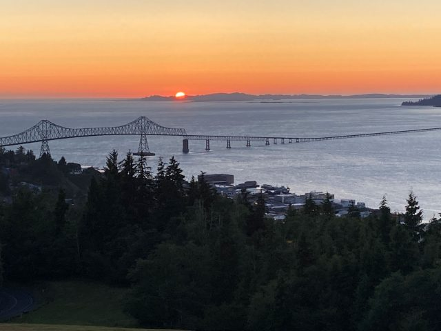 Sunset over water and long bridge