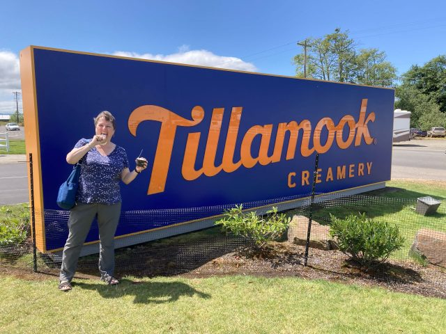 Chris holds ice cream cones by large blue sign saying Tillamook Creamery