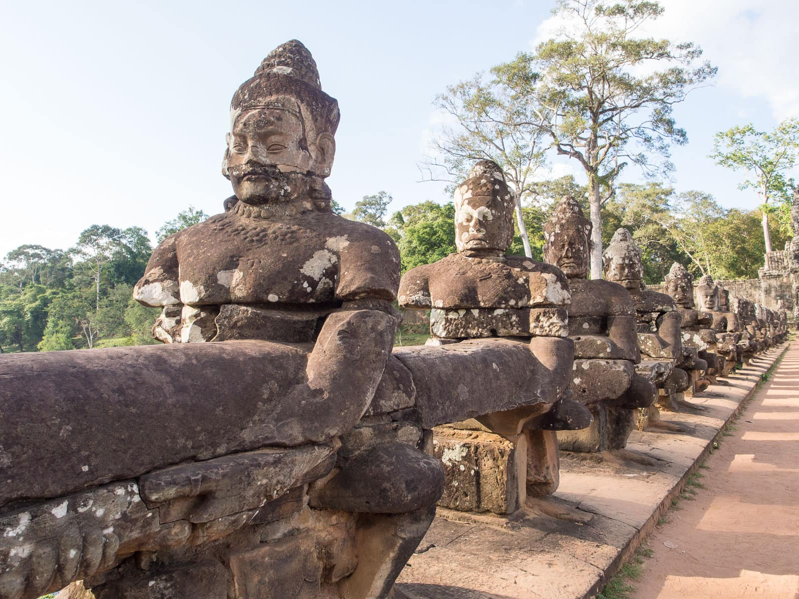 Row of statues of gods holding body of a long snake
