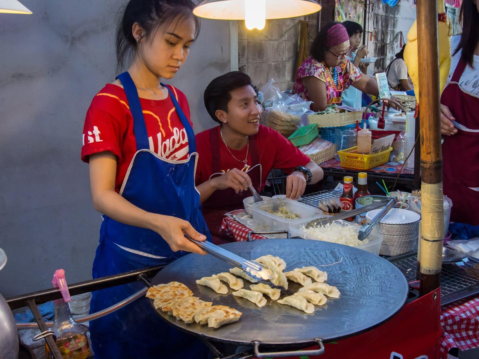 Young woman frying dumplings in night market